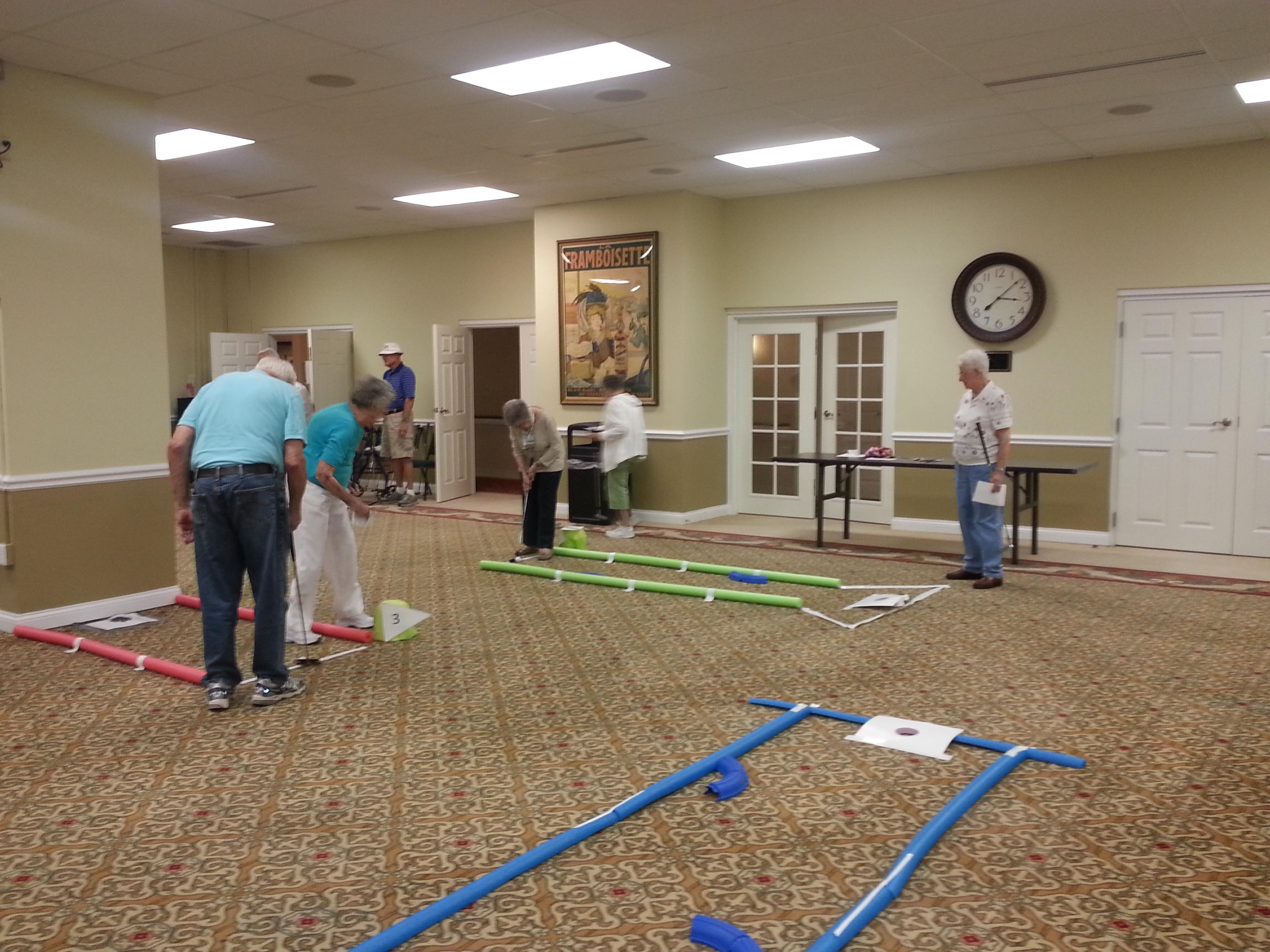 residents on indoor putting course